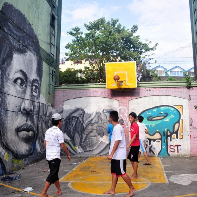 graffiti in public housing yard with makeshift basketball court