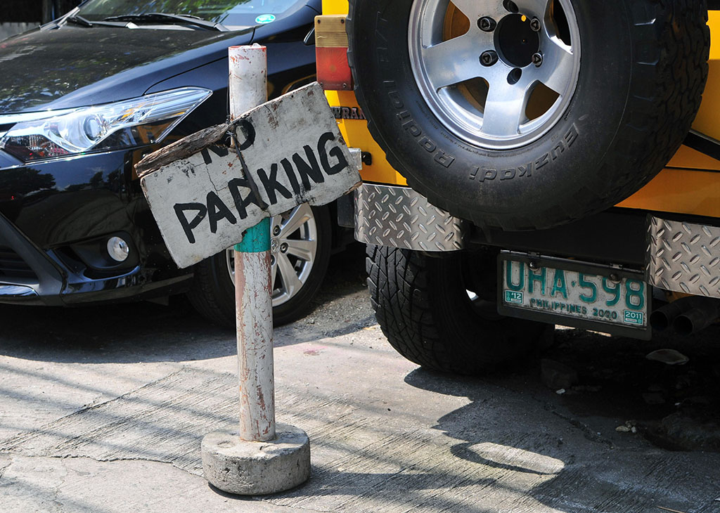 No Parking sign in front of a jeep wrangler