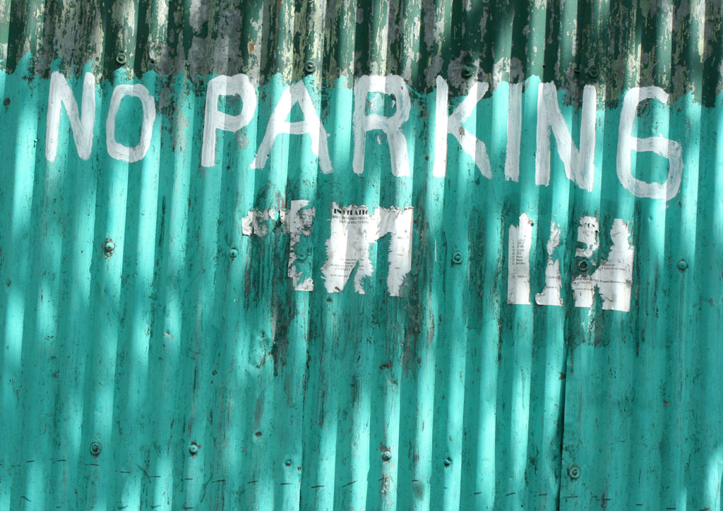 no parking sign on corrugated green wall