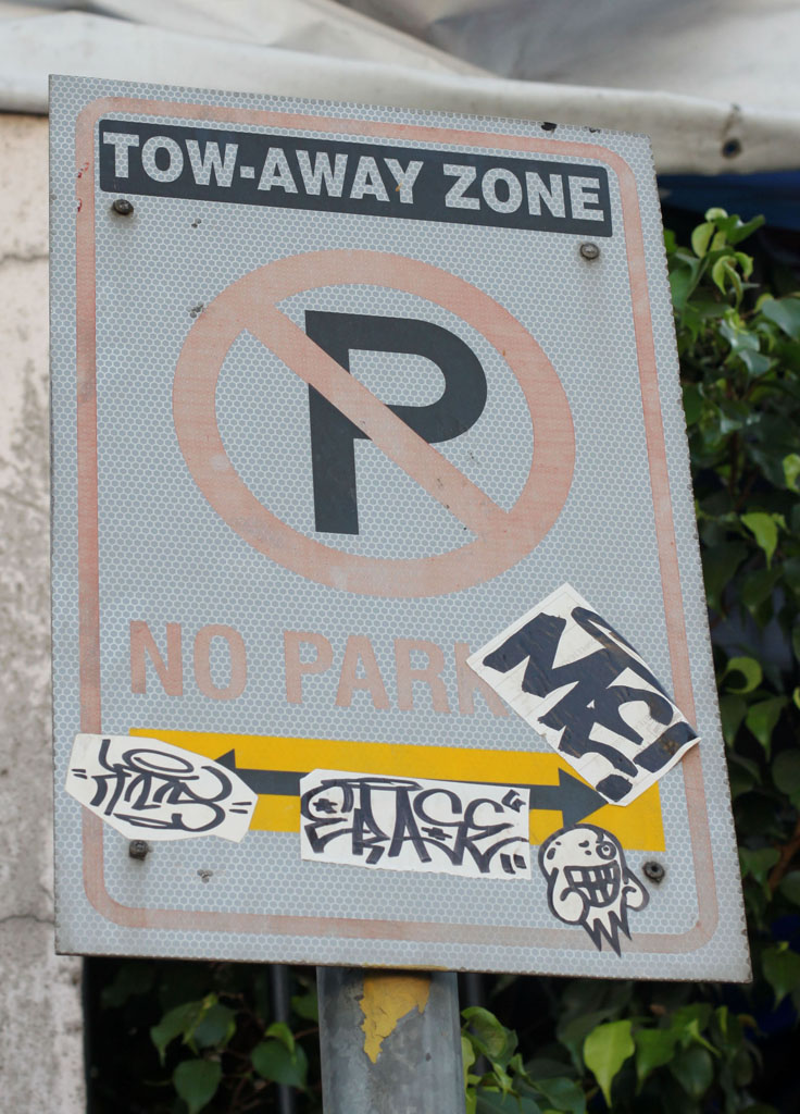 no parking sign with graffiti stickers