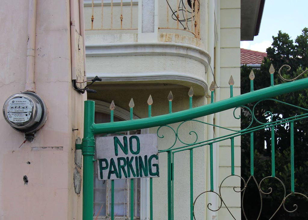 No Parking sign on green gate