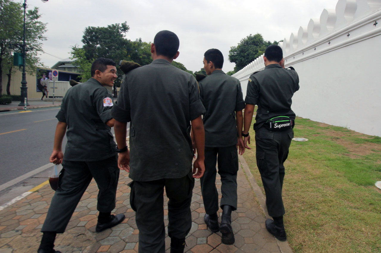 men in uniform walking outside the Grand Palace