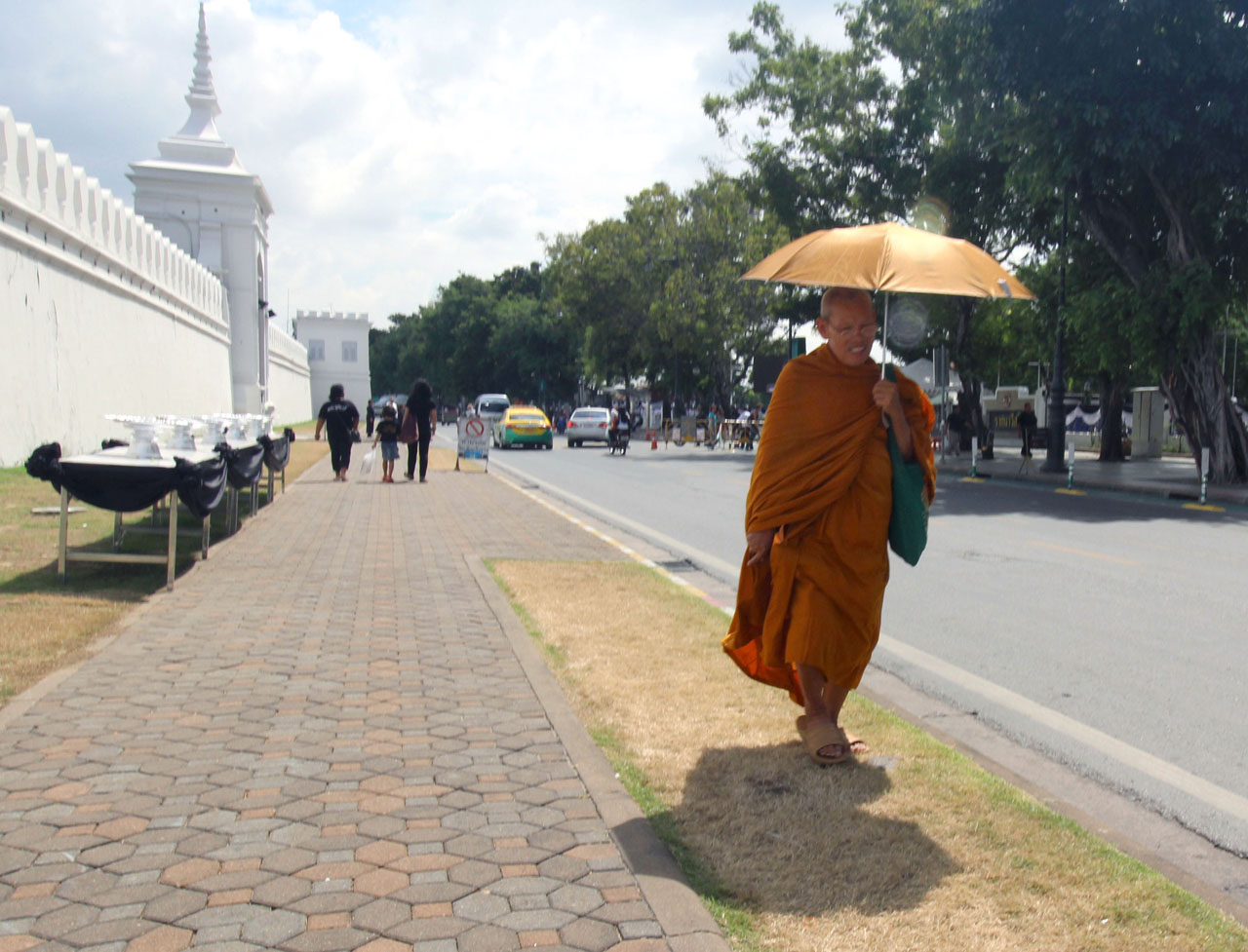 monk walking by people mourning the Thai king near the Grand Pal