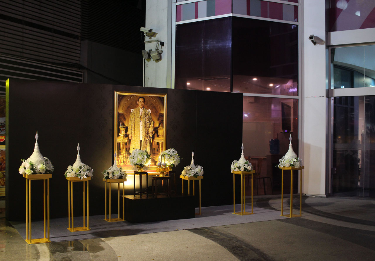 a small memorial to the late king of Thailand outside a mall