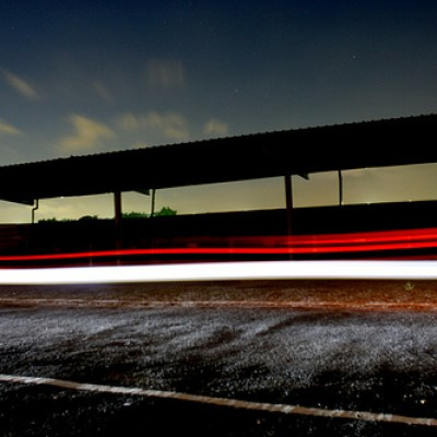 light streaks through a waiting shed at night