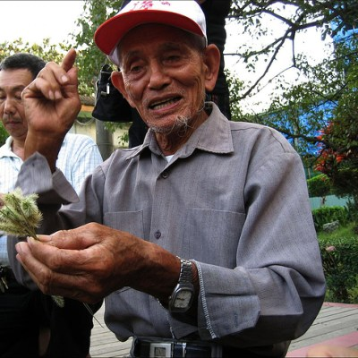 old man making a grass squirrel