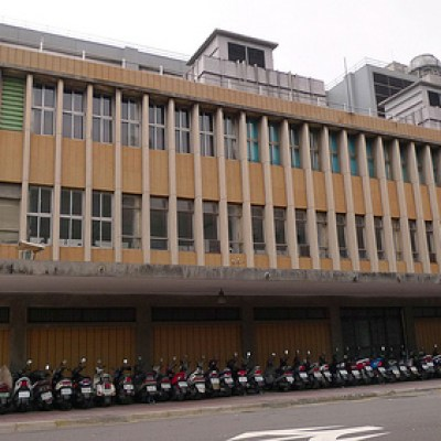 old taipei city building with a row of scooters parked below