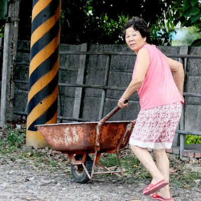 pushing a wheelbarrow in an all-pink outfit