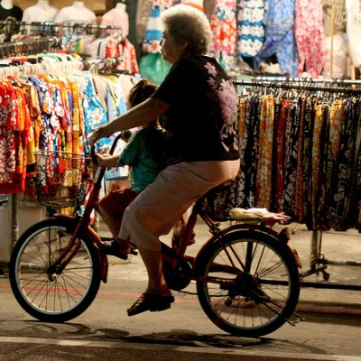 old woman biking with small girl in front of floral shirt shop