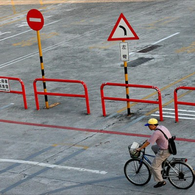 man biking by in a yellow cap