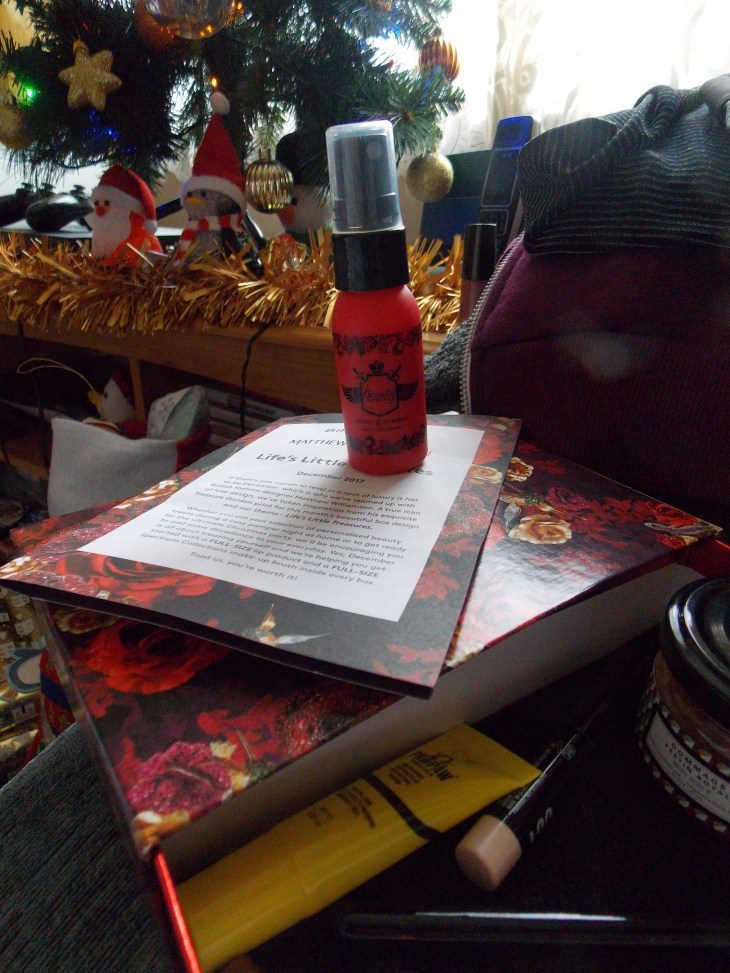 "A product picture of a ""protect and detangle conditioner"" in a small red spray bottle, on top of the ""Birchbox"" mape-up subscription box."