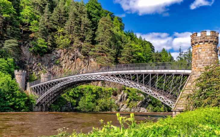 A huge bridge with castle like pillars either side holding it up over a river and with a mountain filled with trees in the background