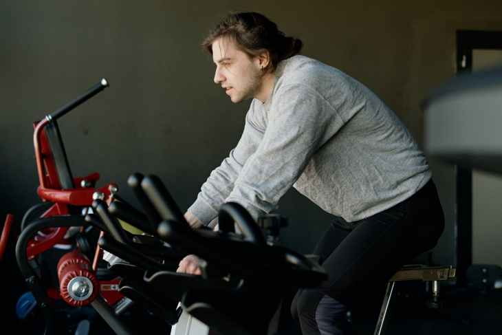 A man on a workout bike at the gym.