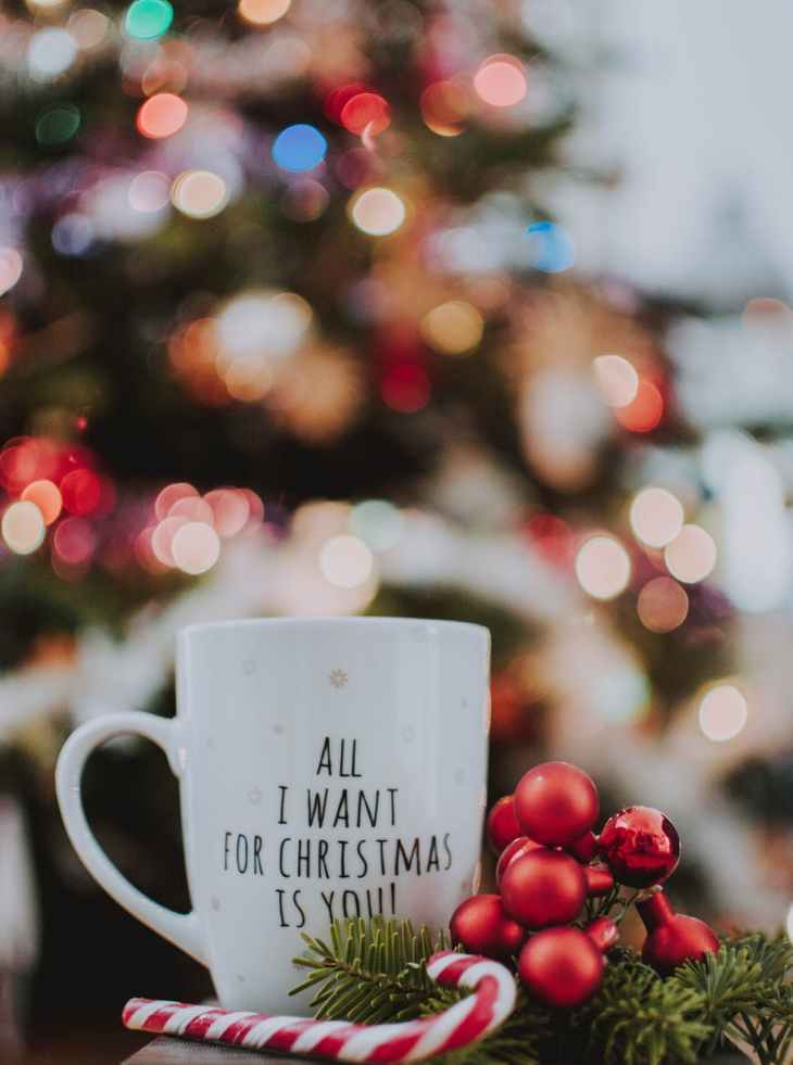 "A white Christmas mug that says ""All I want for Christmas is you!"" with white snowflakes all over it, and some red baubles, a candy cane and some trees cut up next to it. In front of a blurred Christmas tree"