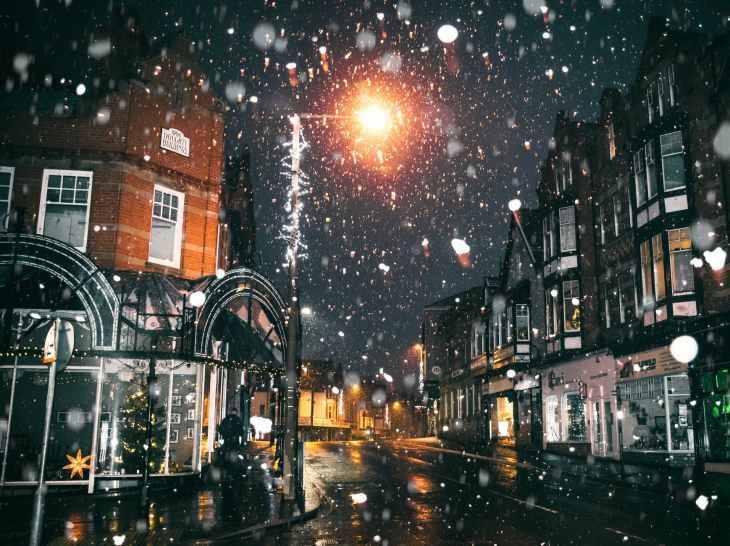A town shot with captures of snow falling down during the evening around Christmas time.