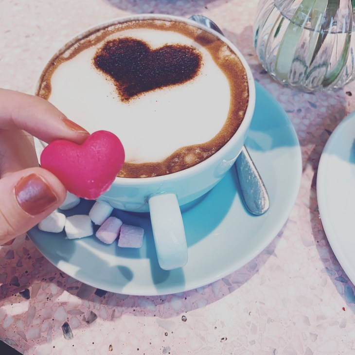 """A hot chocolate with a heart shaped biscuit and marshmellows, inside the """"Peggy Porschen"""" cafe in London."""