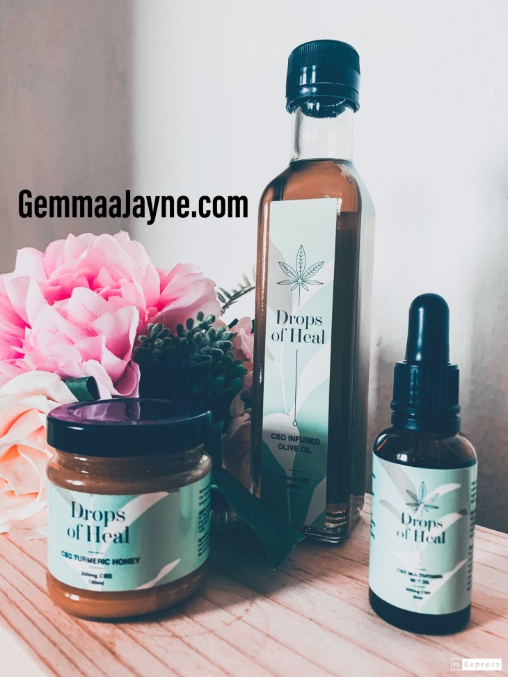 """Product picture of three products from the company """"Drops of heal"""". With  pink flowers in the background."""