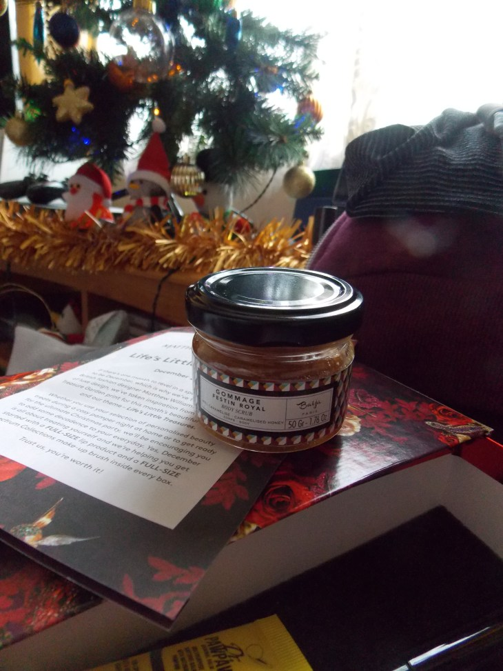 "A product picture of a ""caramelised body scrub"" in a tiny jar on top of the ""Birchbox"" make-up subscription box. In front of a Christmas tree."