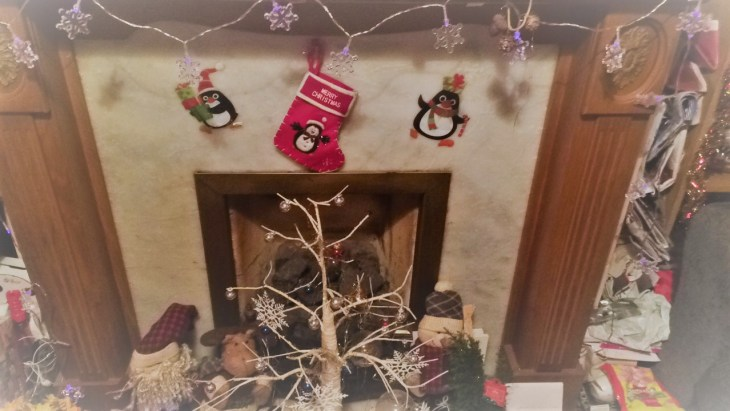 A fireplace with star fairy lights hung over it, a tiny penguin stocking, penguin stickers and a white stick tree with tiny baubles hanging on it.