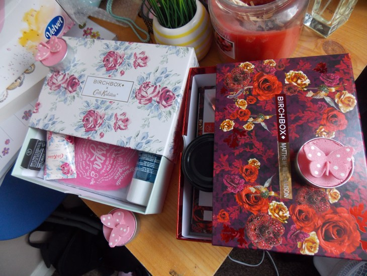 A product picture of two Birchbox products in their boxes. One a white and pink flowery design with some products coming out of it, and the other a red rose theme.