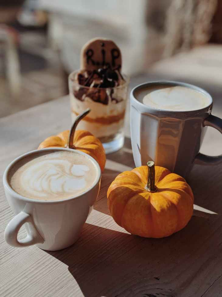 "Two cups of coffee next to two mini pumpkins and a dessert with a ""RIP"" biscuit in it."