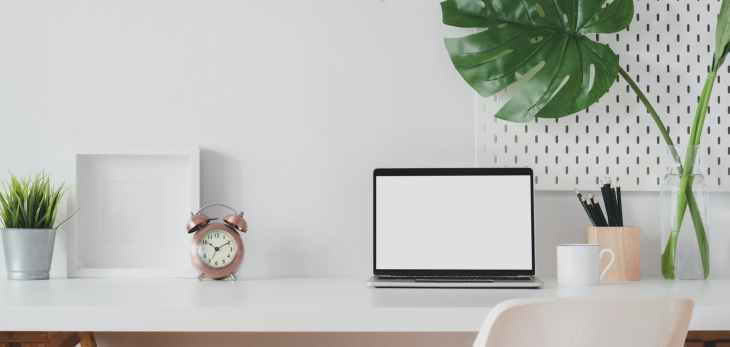 A minimalist and tidy desk area, that is white. There is a laptop next to a cup and a pencil pot and a huge green plant. The other side has a rose gold clock an empty white photo frame and a silver plant pot.
