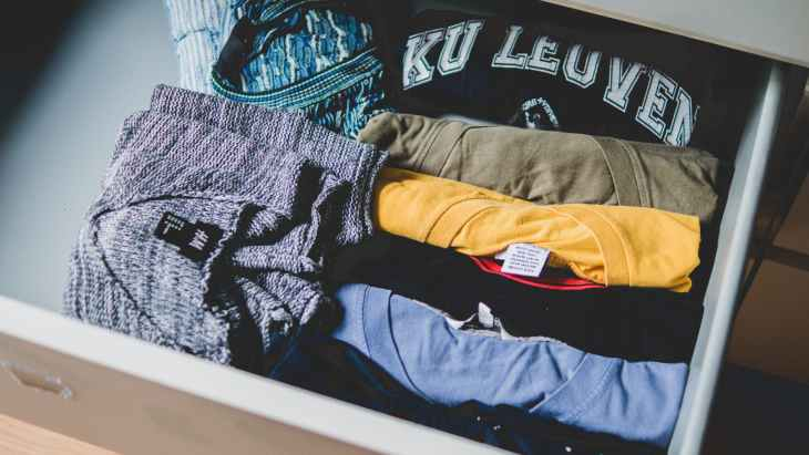 A drawer filled with folded tops and clothes.