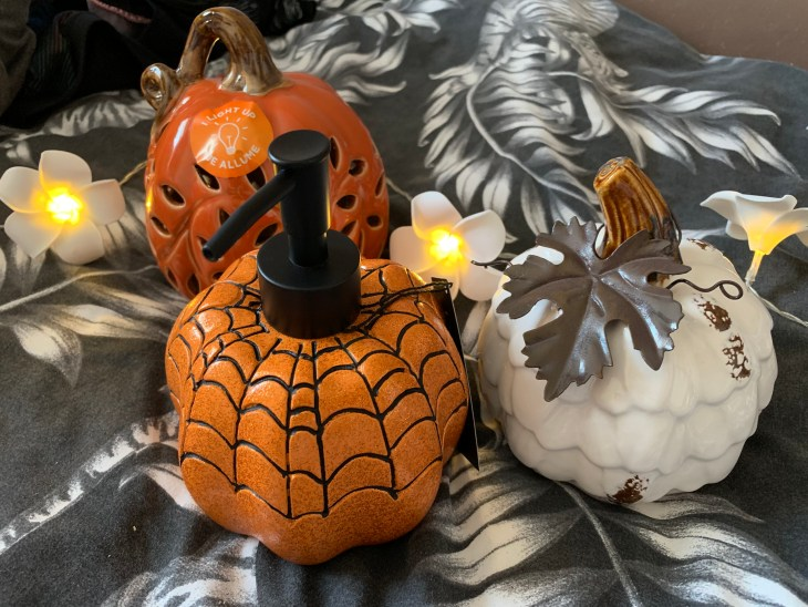 A orange pumpkin soap dispenser, a white china pumpkin and a light up orange pumpkin decor piece on displayed on a bed-sheet with flower lights.
