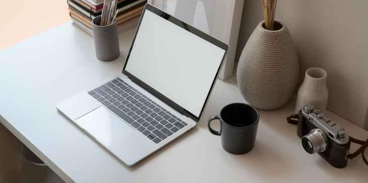 A laptop on a white desk, next to a black mug, camera, a couple of grey vases, a pen pot, stack of books.