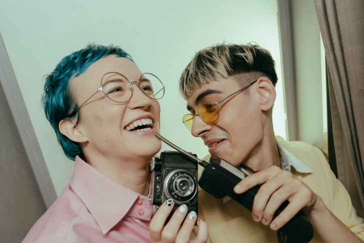 Two people laughing and messing around in a photo booth. One is holding an old phone with an antenna and the other is holding an old camera.