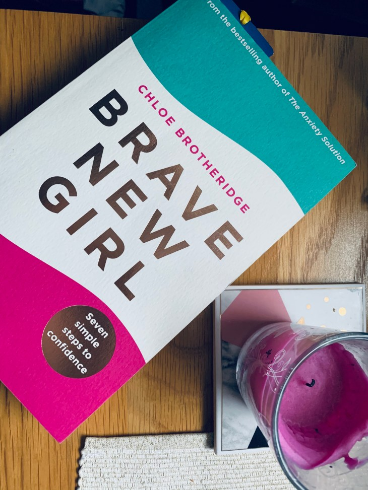 """A book called """"brave new girl"""" on a table next to a cup placemat."""