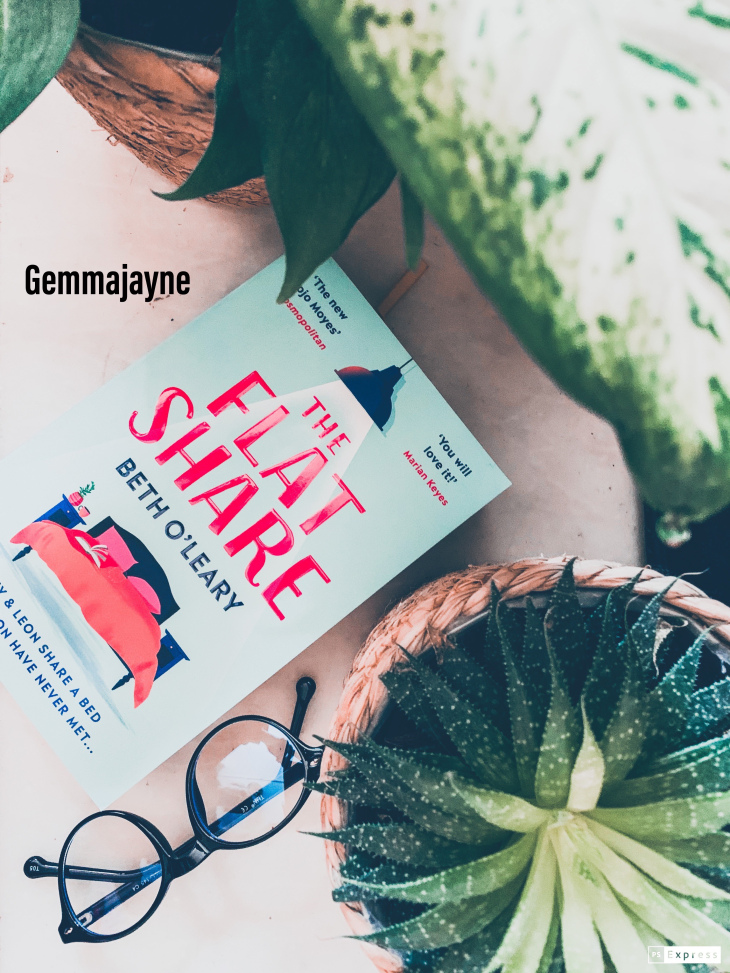 """A book called """"the flat share"""" laying down on a marble background next to a pair of glasses and a green leaf plant."""