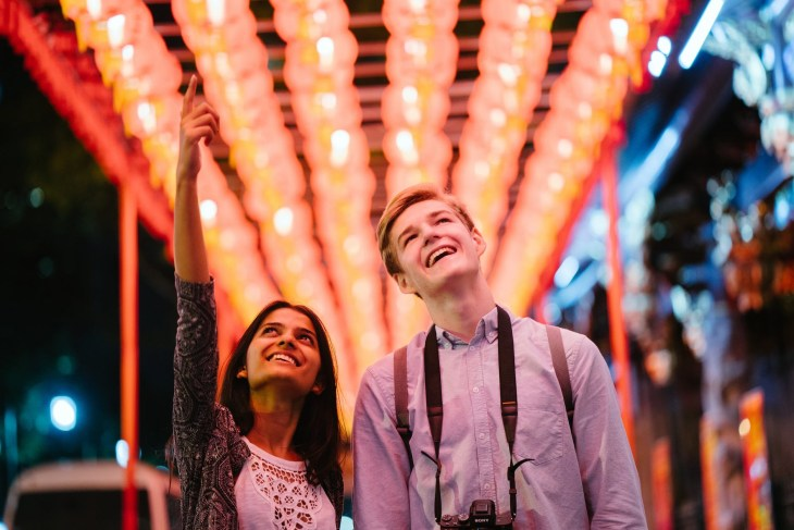 A man and woman smiling whilst looking up at something with loads of lights in the background