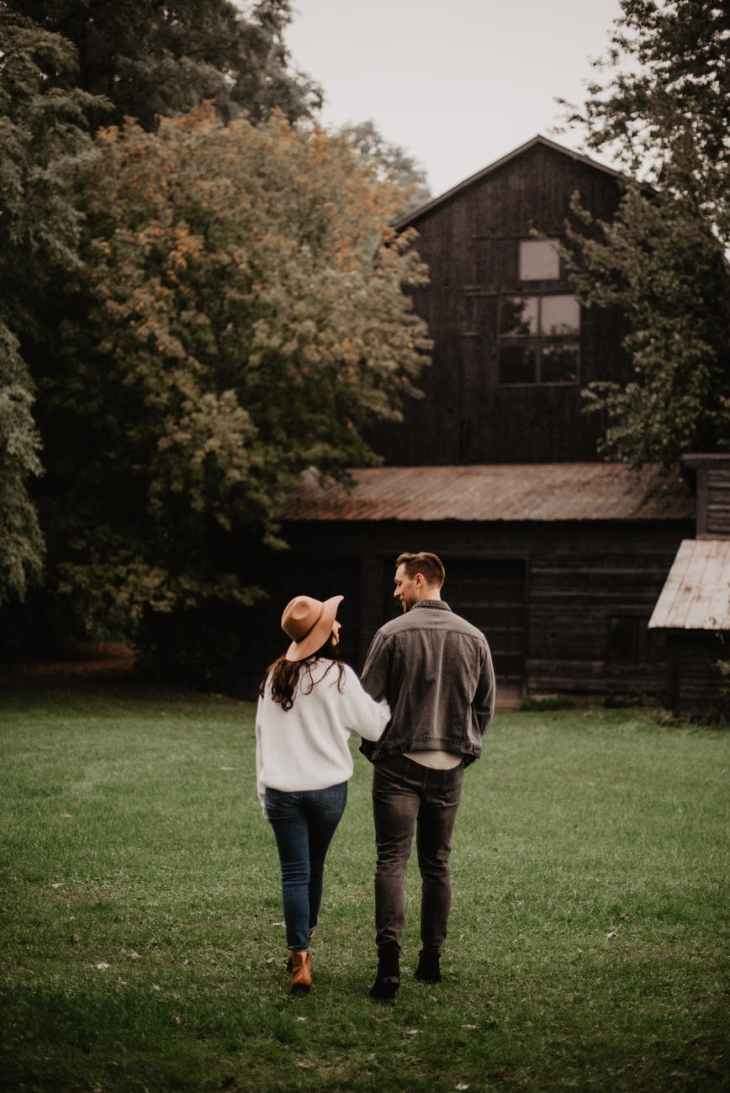 A couple walking towards a huge old brown barn.
