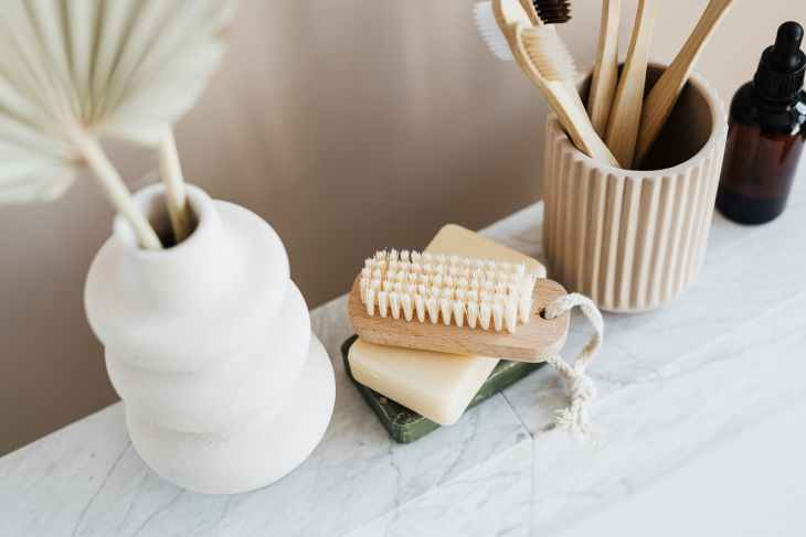 A collection of sustainable items including, a wooden brush and toothbrushes, soap and plant pots.