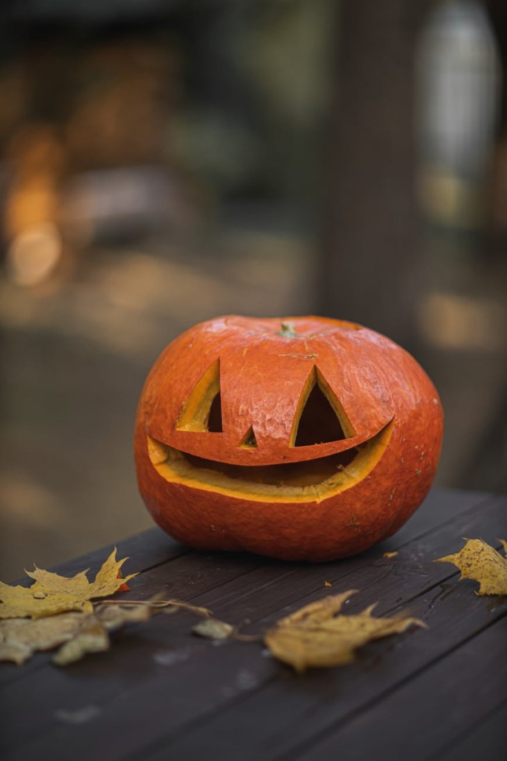 A pumpkin with a carved out smile face.