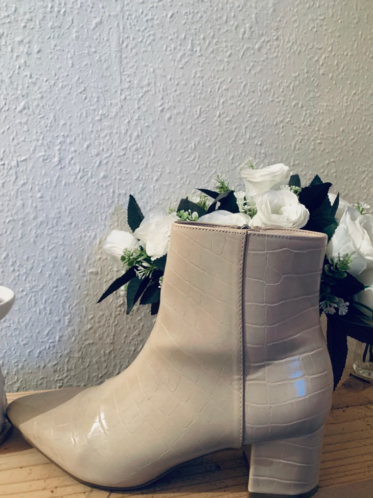 A white boot with a small heel and white roses in the background and a white wall.