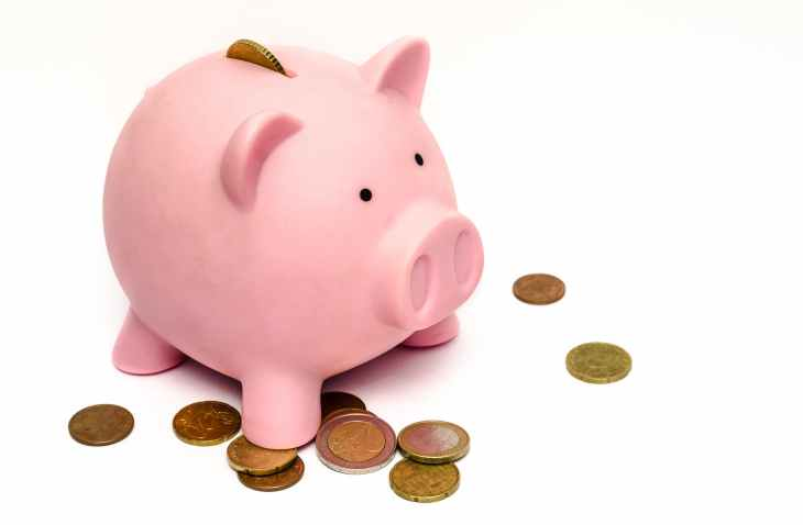 A pink piggy bank with a collection of coins scattered around it and one coin sticking out of the top, encouraging the help to reach financial freedom.