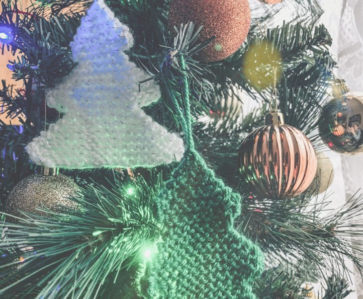 Two knitted Christmas tree's one in white and one green, both hanging on a Christmas tree with other baubles and decorations.