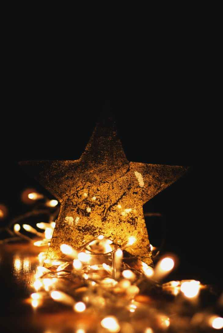 A giant gold star surrounded by fairy lights all lit up whilst in the dark.