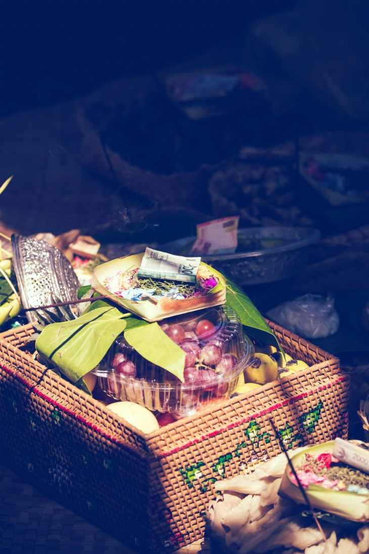 A huge basket filled with food and fruit and flowers on the top.