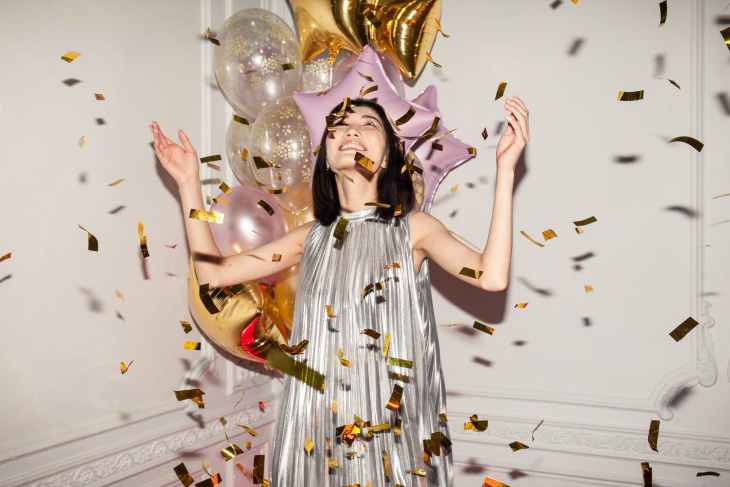 A woman looking up with her hands in the air whilst golden confetti is falling down on her/around her and a selection of pink and gold balloons behind her.