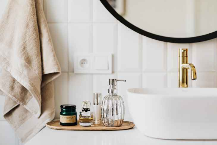 A bathroom set up with a round sink and a gold tap, the edge of a mirror and a bamboo wooden plate with perfume and cleanser's on and a towel hanging up.