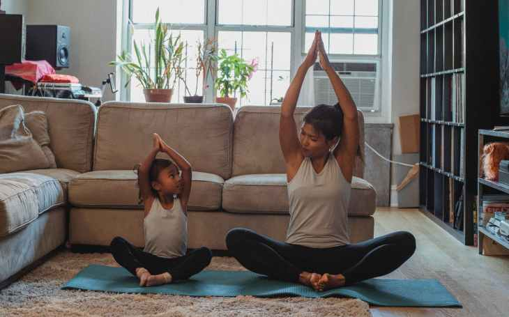 A mother and her child doing yoga together on a matt in their living room in front of the sofa, looking after their fitness.