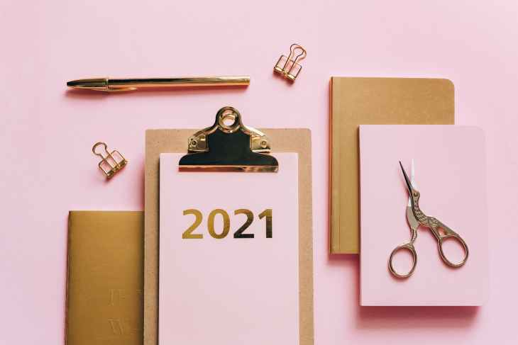 "A pink background, with a brown clipboard with ""2021"" on pink paper in gold writing attached to the clipboard. next to brown notebooks and one pink notebook with some scissors on top of them."