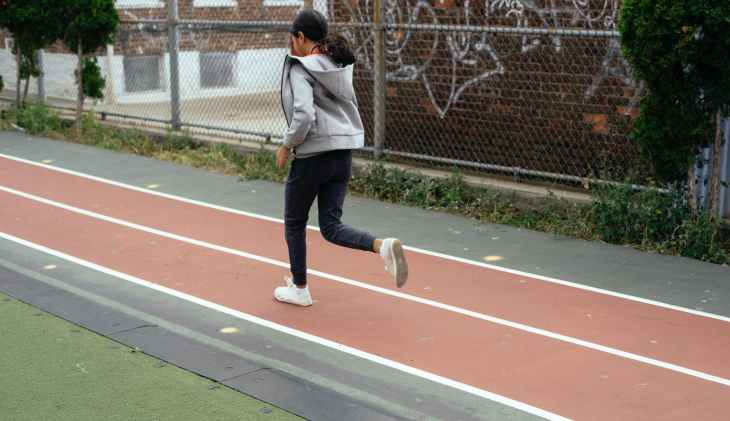 A girl running along a track on a running course, in a tracksuit facing away from the camera.