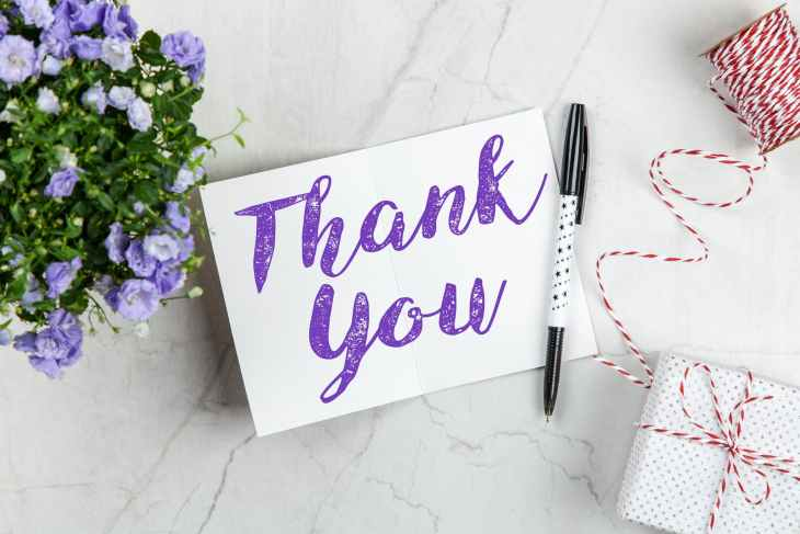 "A card with ""thank you"" wrote on it in purple writing. Next to purple flowers and a present with string."