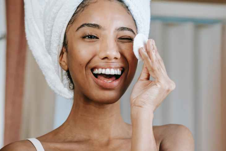 A woman smiling with one eye closed whilst looking at her self in the mirror. Whilst her hair is in a hair towel and she is cleaning her face with a cloth.