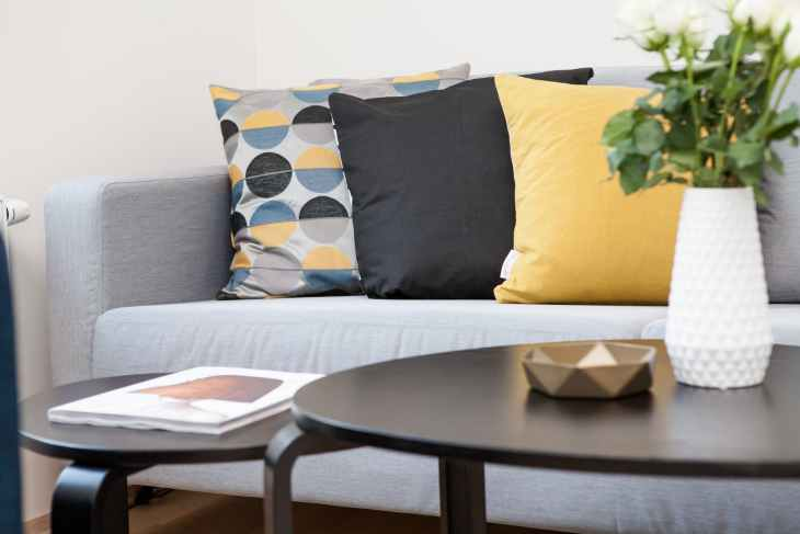 centerpiece on coffee table beside sofa with three pillows in a clutter free home
