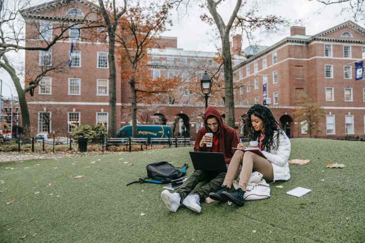 woman in white long sleeve shirt sitting on green grass field. Tips you should know as a University student